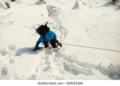 Climber pulls on a rope railing on a snowy mountain slope.