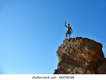 Climber Raising Hand On Top Of Mountain. 
