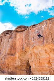 Climber rappelling down a cliff in Mitzpe Ramon crater, Israel. Abseiling, rappel and climbing concept.