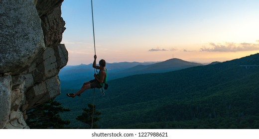 Climber rappels from a beautiful cliff with the Blue Ridge Parkway in the background at sunset