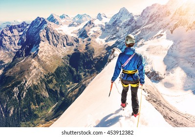 Climber reaches the summit of mountain peak. Climbing and mountaineering sport concept.