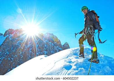 Climber reaches the summit of mountain peak. Climbing and mountaineering sport concept