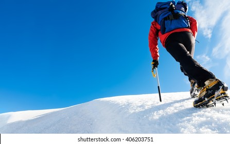 A climber reaches the top of a snowy mountain. Concept: courage, success, perseverance, effort, self-realization. Mont Blanc, Chamonix, France.
