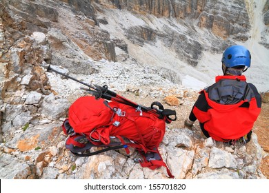 Climber resting near the backpack, Dolomite Alps, Italy