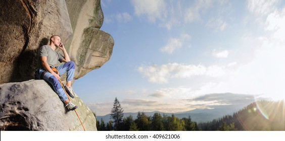 Climber is sitting on the big natural boulder secured with the rope against blue sky and mountains. Young man is talking on the cell phone at the mountains. Summer time. Copy-space on the right.