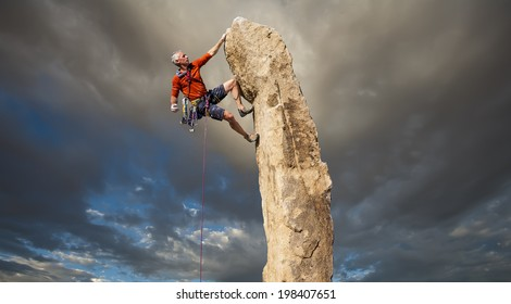 Climber struggles for his next grip on the edge of a challenging cliff.