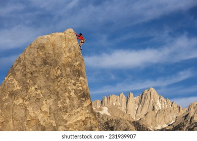 Climber struggles to the summit of a challenging cliff.