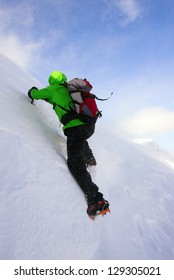 Climber surpassing a cornice in the Fagaras mountains, Romania. The high wind is creating a swirl, blowing snow particles over the climber