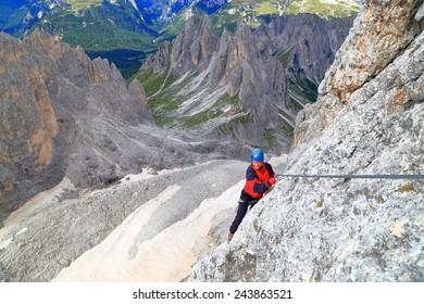 "Climber traversing high above ground along the steel cable of via ferrata ""Merlone"" in Cadini di Misurina, Dolomite Alps, Italy"