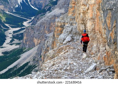"Climber walking aerial ledge on via ferrata ""Lipella"", Tofana massif, Dolomite Alps, Italy"