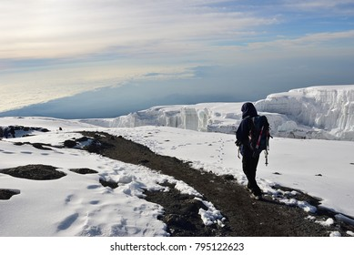 Climber walking round the rim of crater returning to Gilmans Point after visiting Uhuru Peak the summit of Mt Kilimanjaro. Tanzania, Africa