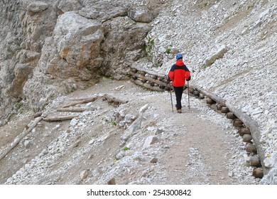 Climber walking the trail to Pomedes refuge, Tofana massif, Dolomite Alps, Italy