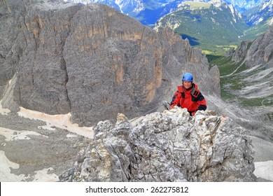 "Climber woman arriving on top of the mountain on via ferrata ""Merlone"", Cadini di Misurina, Dolomite Alps, Italy"