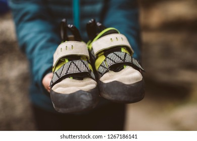 Climber woman with her climbing shoes placed on her hands.
