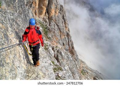 """Climber woman on traverse section of via ferrata """"Punta Ana"""", Tofana massif, Dolomite Alps, Italy"""
