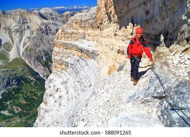 """Climber woman traversing along steep wall on via ferrata """"Lipella"""", Tofana massif, Dolomite Alps, Italy"""