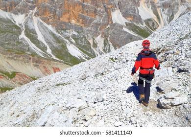 """Climber woman walking on rocky trail on via ferrata """"Lipella,"""" Tofana massif, Dolomite Alps, Italy"""