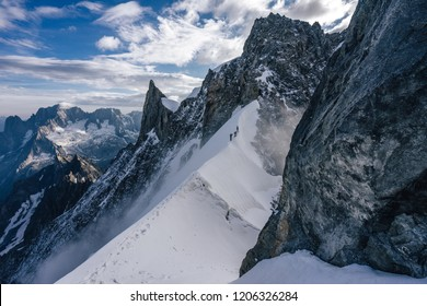 Climbers or alpinist on a knife sharp ridge of an alpine peak or summit of Aiguille du Rochefort. Alpine landscape and adventure climbing ascent in Mont Blanc Massif. Alpinism in high mountains.