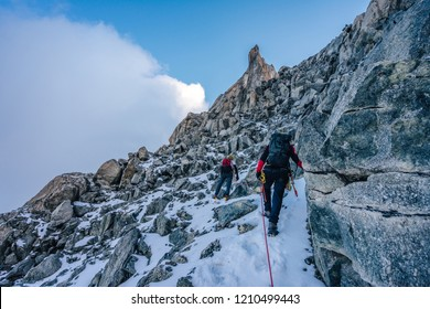 Climbers and alpinists climbing hiogh alpine ridge with snow and rocks. Adventure extreme ascent of an alpine peak Aiguille du Rochefort in Mont Blanc Massif, Chamonix. Climbers with helmets.