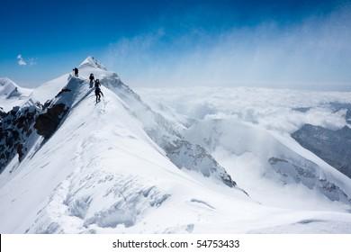 Climbers balancing in blizzard on a narrow ridge of Lyskamm (aka Maneater, 4480 m)