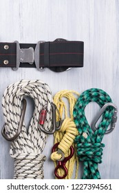 climber's belt with different ropes and carbines for insurance lie on a light background