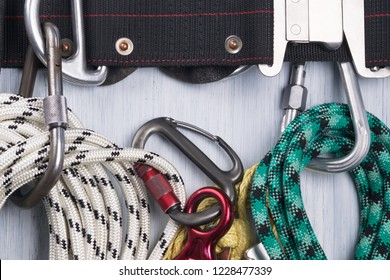 climber's belt with different ropes and carbines for insurance lie on a light background, close-up