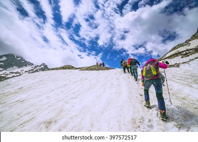 climbers climbing mountain with snow field
