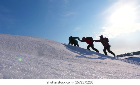 climbers holding hands helping each other climb snowy hill. well-coordinated teamwork in winter tourism. team of travelers in winter go to their goal of overcoming difficulties.