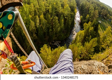 Climber's legs hanging on a rope in a harness, first person view to river in forest