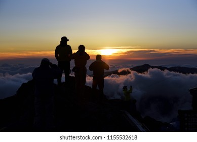 Climbers looking at sunset from the top of the mountain