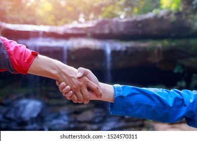 The climbers on the cliff pulled their hands together, two people helping each other.Two tourists shaking hands,Successful business people handshaking