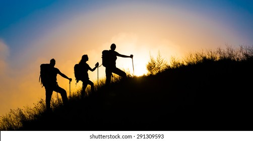 Climbers on grassy hill. Family three people silhouette walking up steep grassy hill majestic sunrise and blue sky background