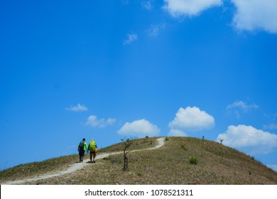 Climbers on the grassy hill. Royalty high-quality free stock image of a group walking up steep grassy hill majestic on a sunny day and blue sky background in summer