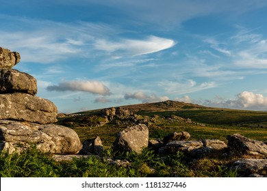 Climbers on Weathered granite outcrops at Saddle Tor and Rippon Tor, Dartmoor National Park, Devon in warm evening light