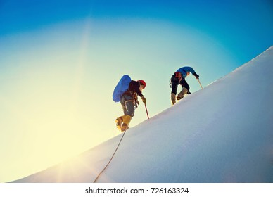 Climbers  reaches the summit of mountain peak. Success, freedom and happiness, achievement in mountains. Climbing sport concept.
