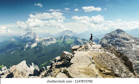 Climbers silhouette standing on a cliff in Dolomites. Tofana di Mezzo, Punta Anna, Italy. Man Celebrate success on top of the mountain Hiker standing on rocky ridge and enjoying  the view in Dolomites