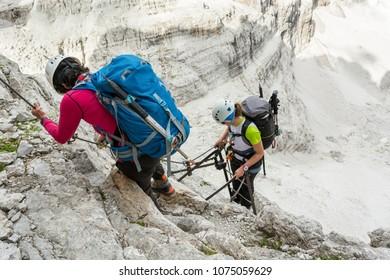 Climbers tackling via ferrata metalic ladder.