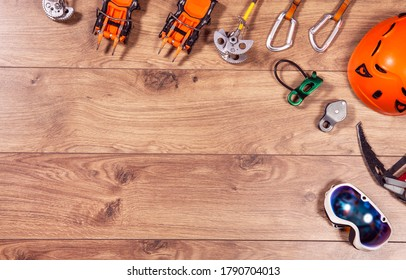 Climbing adventure equipment flat lay view. Top view of extreme mounteneering tools like helmet, campons, ice axe, carabiner, glasses. Copy space on wood.