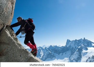 Climbing in Chamonix. Climber on the stone wall of Aiguille du Midi in Mont Blanc, France. Large copy-space on the right. Concepts: determination, concentration, effort, strength, team work.