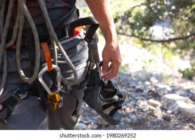 Climbing equipment on a male climber: rock shoes, rope, quickdraw, safety device, harness. Sports mountain tourism, active lifestyle, extreme sports