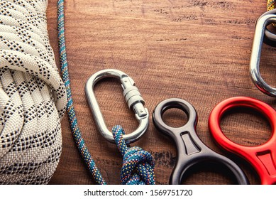 Climbing equipment outdoor for a Mountain trip or Rescue With rope carabiners ascender belay/rappel device, over concrete background with copy space on wooden background, top view. Travel concept