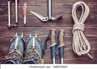 climbing equipment: rope, trekking shoes, crampons, ice tools, ice ax, ice screws, red knife and other set on dark wooden background, top view. Travel concept.