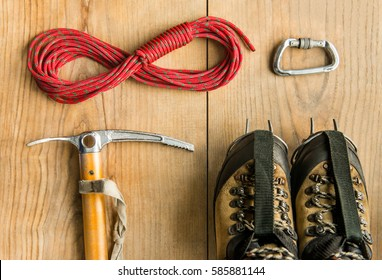 climbing equipment: rope, trekking shoes, ice tools, ice ax, crampons, carbine on wooden background, top view