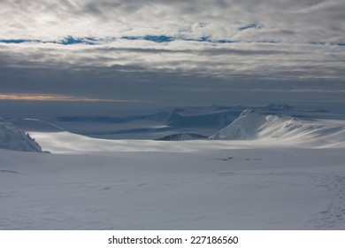 Climbing expedition on Mount Vinson, Sentinel Range, Ellsworth Mountains, Antarctica. View over the climbers in the base camp, dramatic skies in the background. Vinson is one of the 7 Summits.