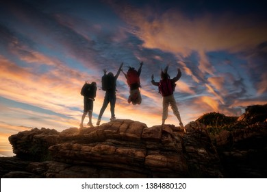 Climbing group friends jumping on top mountain and amazing sunset sky .Teamwork , Helps ,Success, winner and Leadership concept .