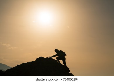 Climbing hiking silhouette in mountains and ocean, rock climber in inspirational sunrise landscape on mountain peak. Accomplished fit man on sunrise adventure and lifestyle concept.