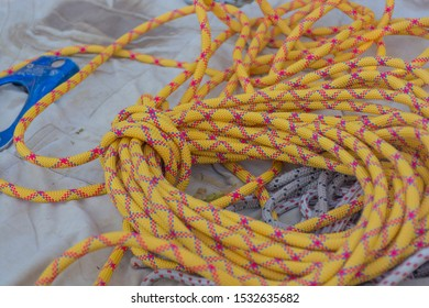 Climbing rope coiled up and knotted for transportation, placed on the light cloth outdoor. Active leisure - rappelling, mountain climbing