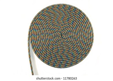 Climbing rope curled into a spiral on a white background for use as a background for adventure sport concept