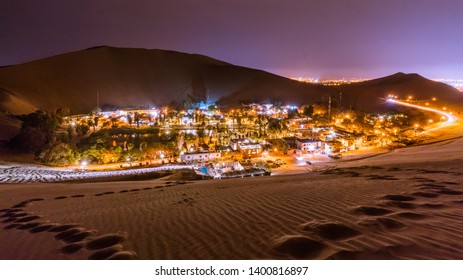 Climbing up the sand dunes here in Huacachina/Peru in order to take a nice landscape picture of this Oasis