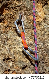climbing shackles and rope on a rock wall vertical escalation